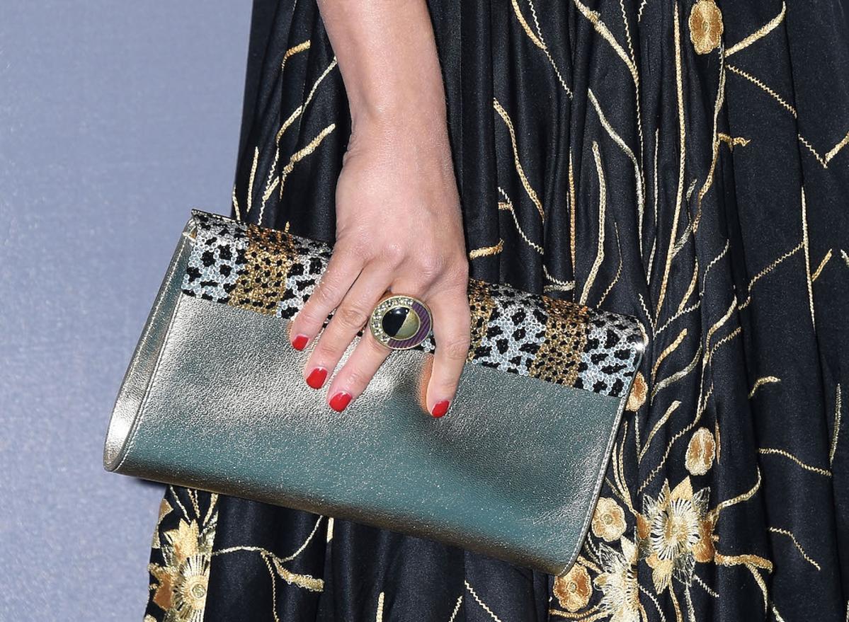 Iza Miko na długiej czarnej sukni ze złotymi ozdobami, metaliczną torebką w koku na czerwonym dywanie