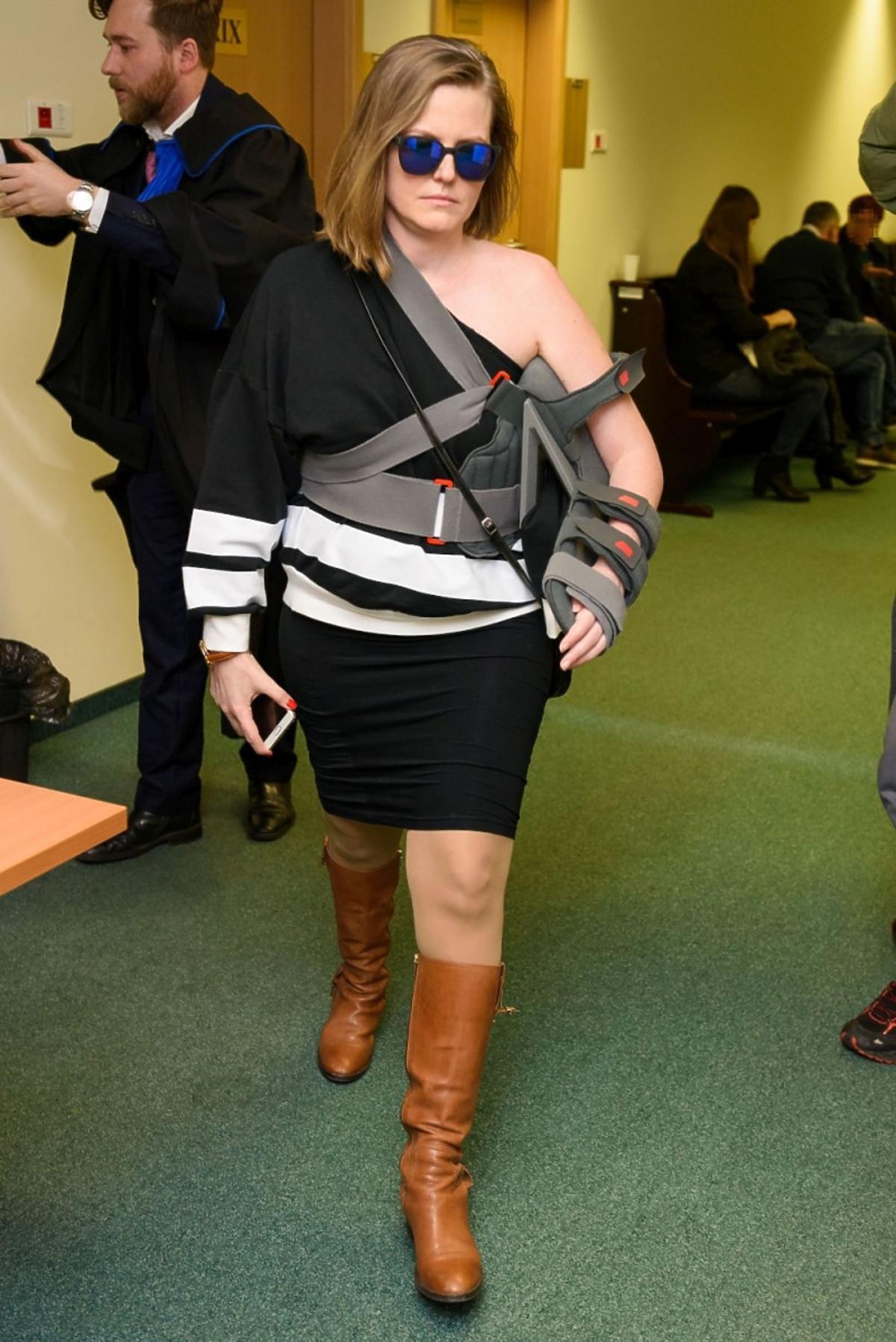 Izabela Marcinkiewicz z unieruchomiona ręką i okularach przeciw słonecznychw sądzie