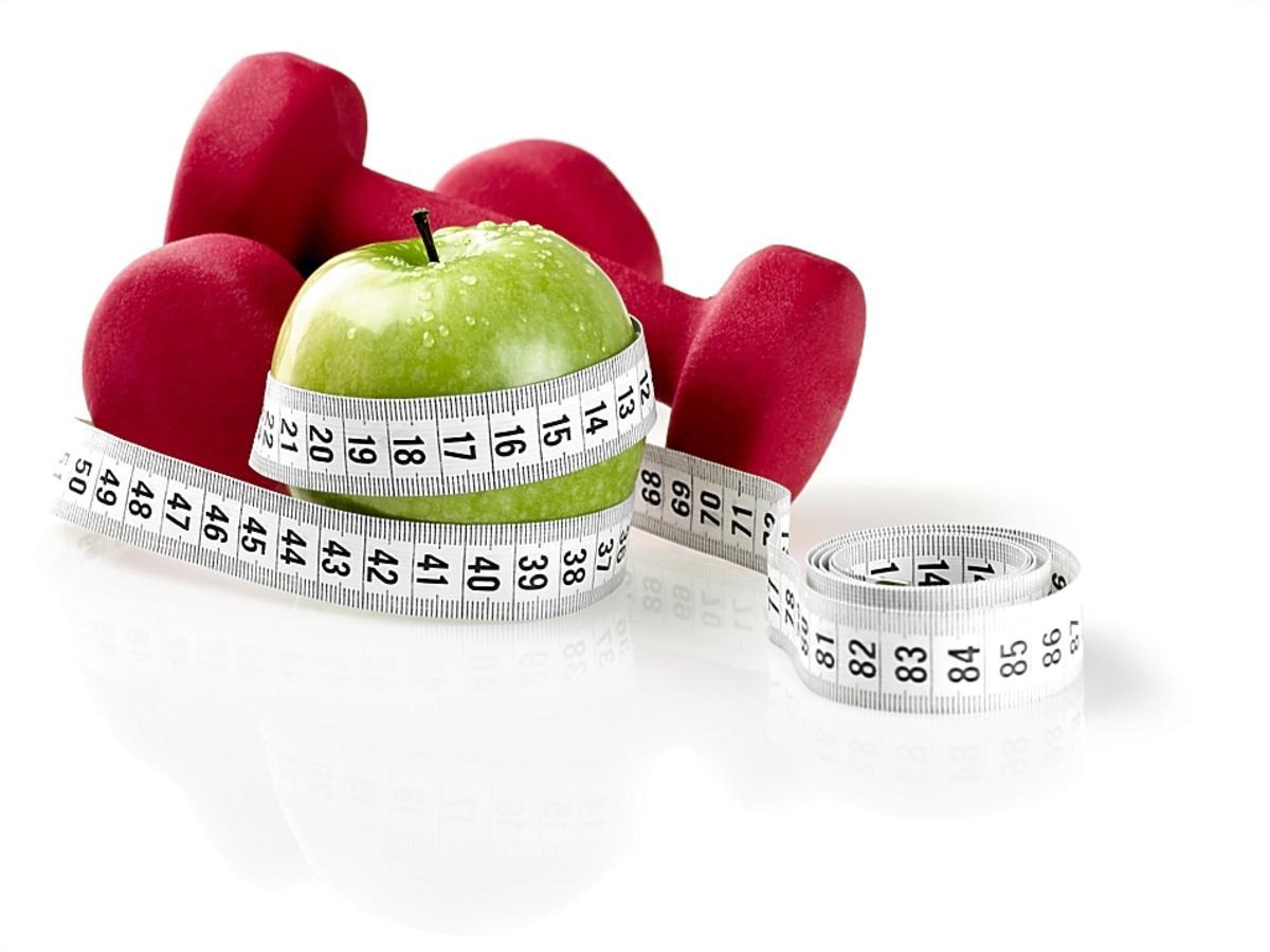 jabłko oplecione centymetrem i hantelki