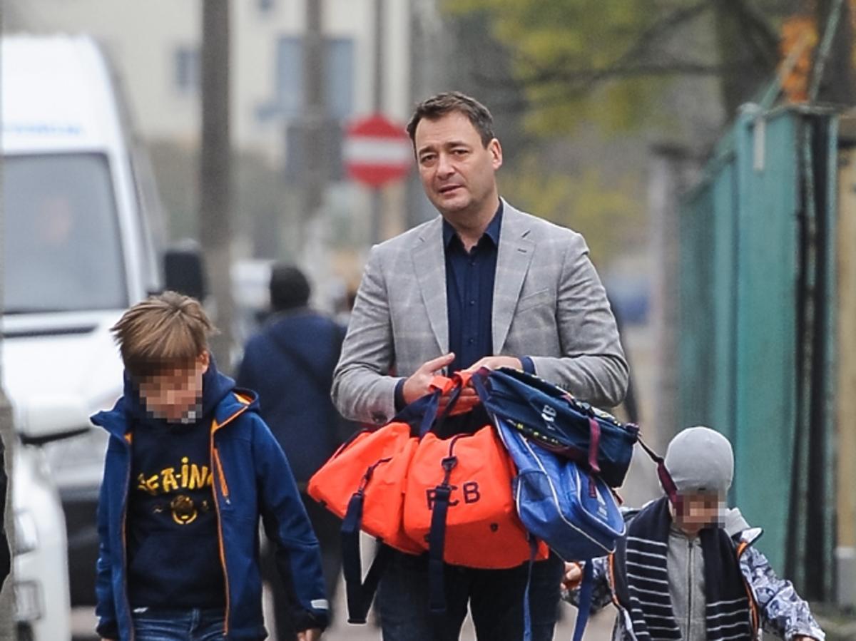 Jacek Rozenek jasnej marynarce z synami Stanisławem i Tadeuszem na ulicy