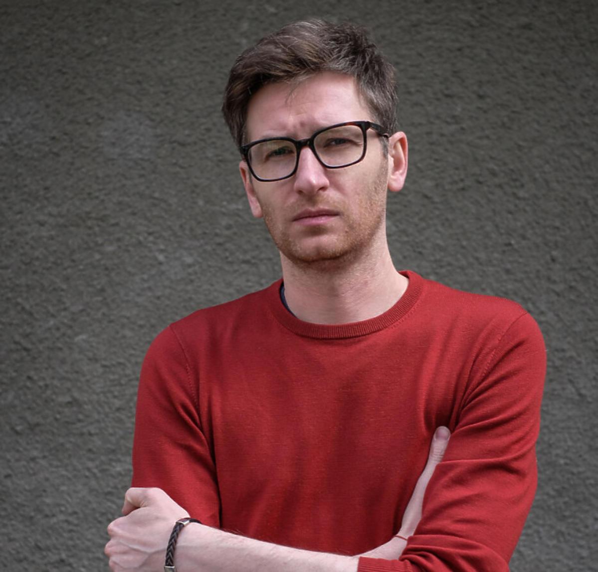 Jarosław Tumidajski w czerwonym swetrze