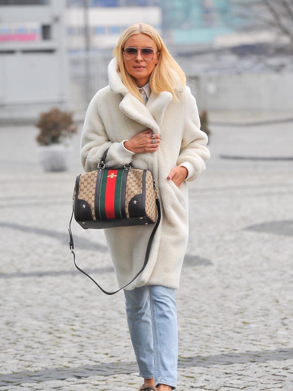 Joanna Horodyńska w białym płaszczu z futerka z kolorową torebką