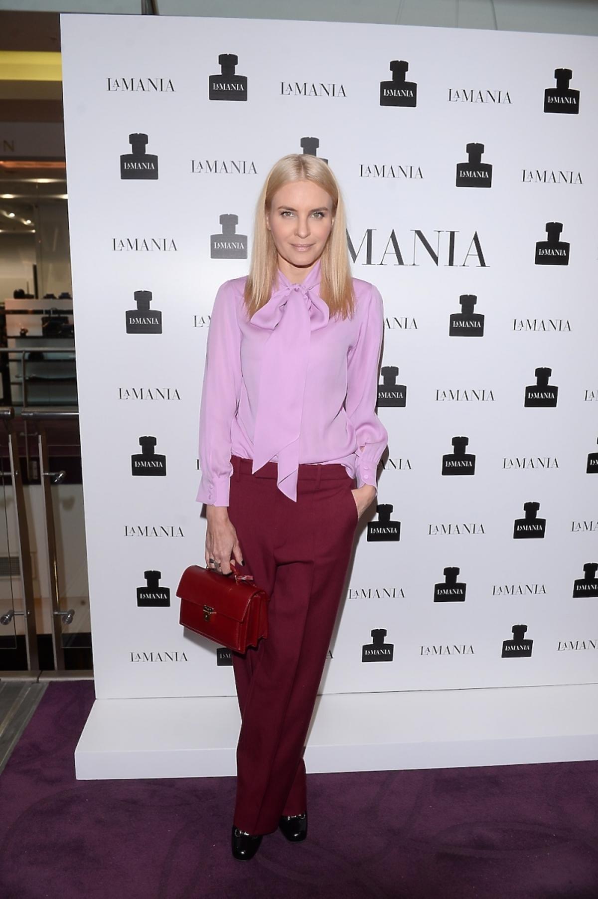 Joanna Horodyńska w blond włosach, różowej koszuli Gucci, w bordowych spodniach Gucci i z bordową torebką Saint Laurent