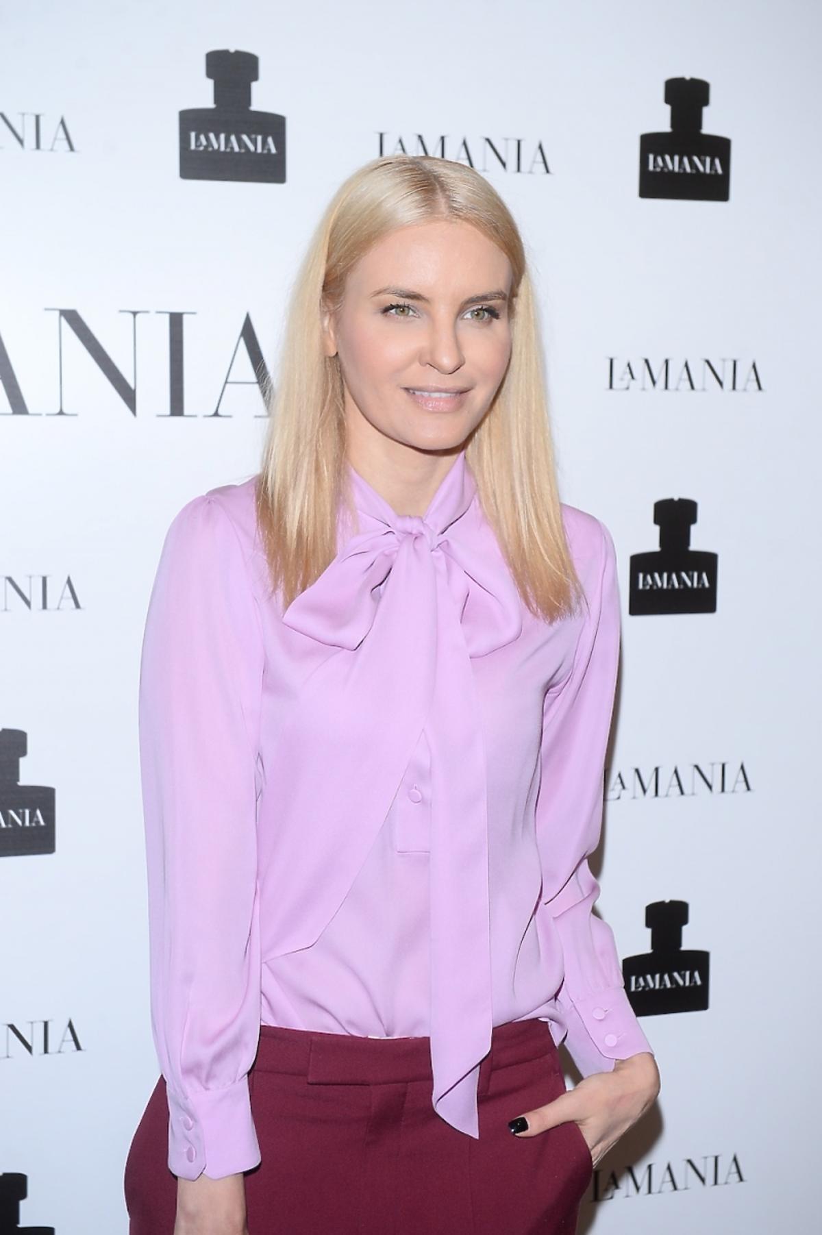 Joanna Horodyńska w różowej koszuli z kokardą i w bordowych spodniach