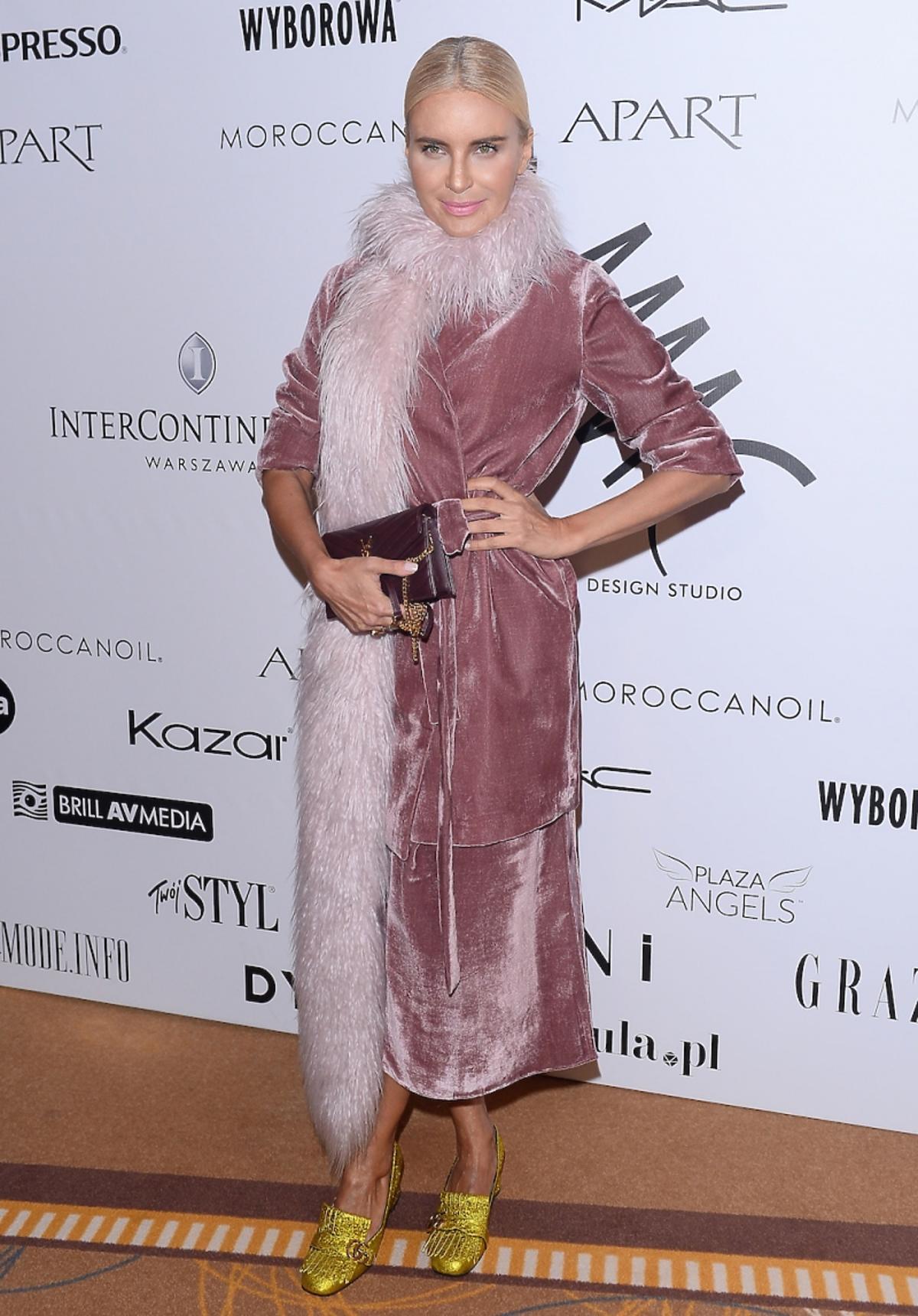 Joanna Horodyńska w różowej marynarce, sukience i futrzanym szalu, bordową torebką i złotych błyszczących butach