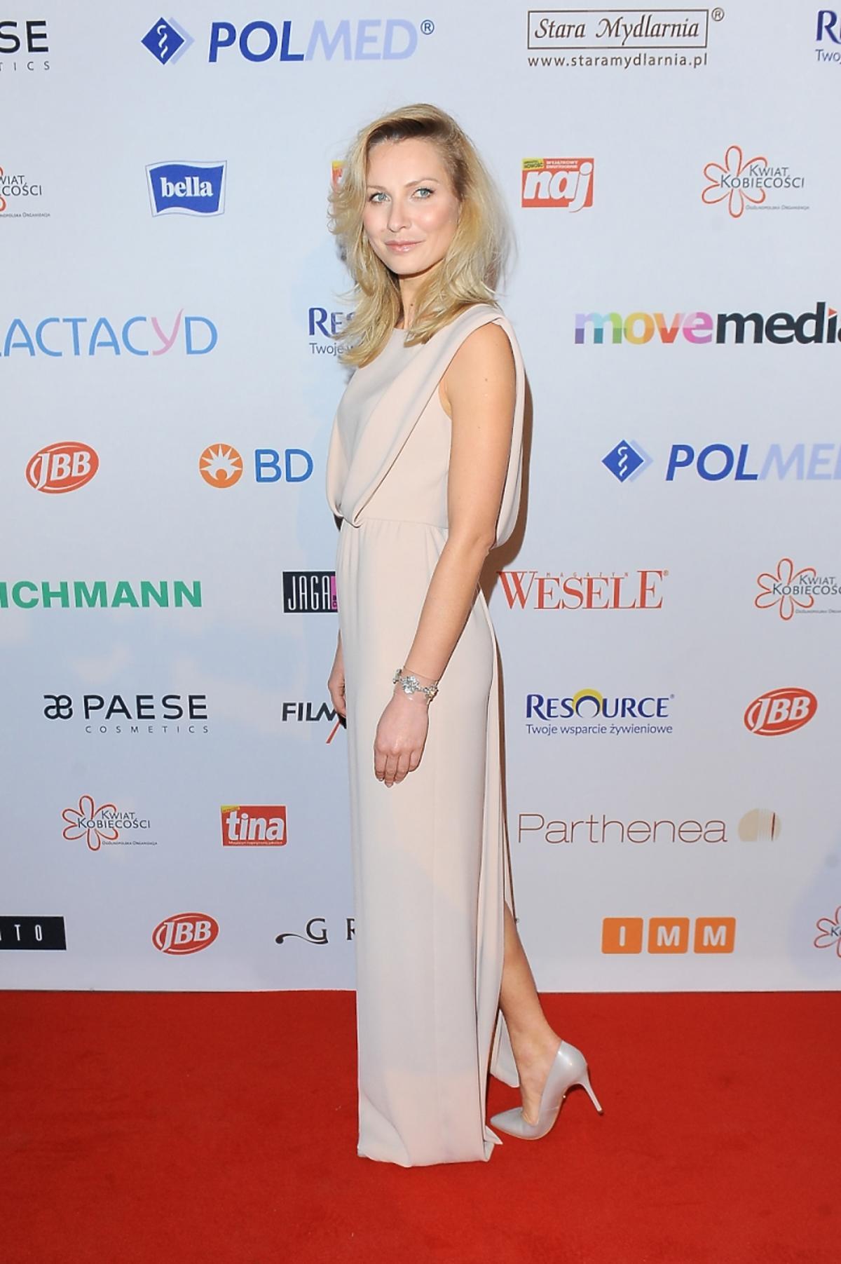 Joanna Moro w długiej kremowej sukni bokiem z odkrytymi ramionami