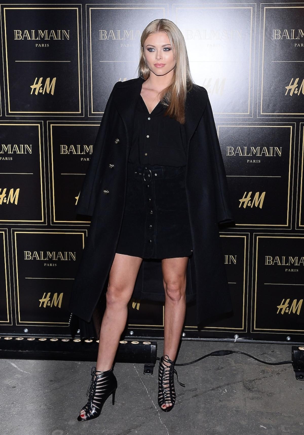 Joanna Opozda w czarnynm płaszczu koszuli i sandałach