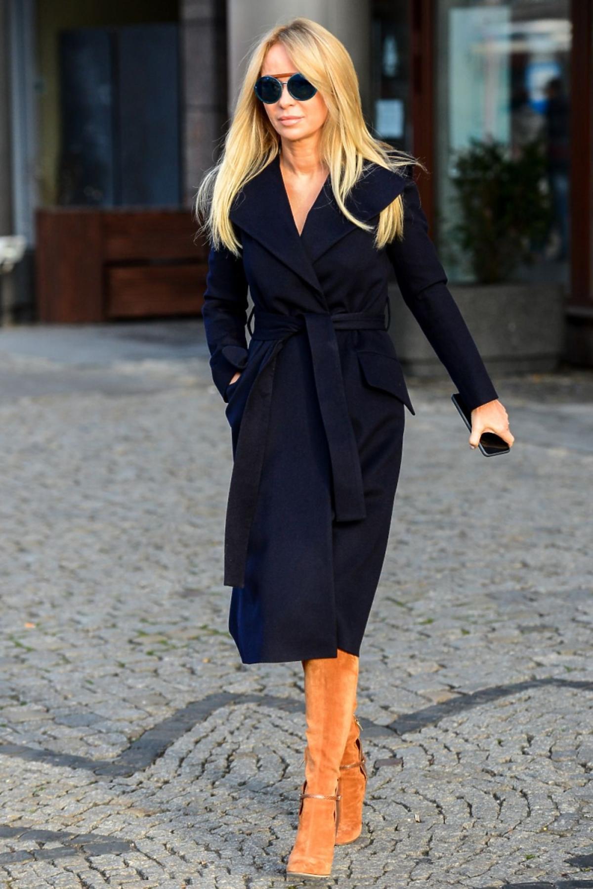 Joanna Przetakiewicz w niebieskim płaszczu i brązowych zamszowych  butach przed studiem telewizyjnym