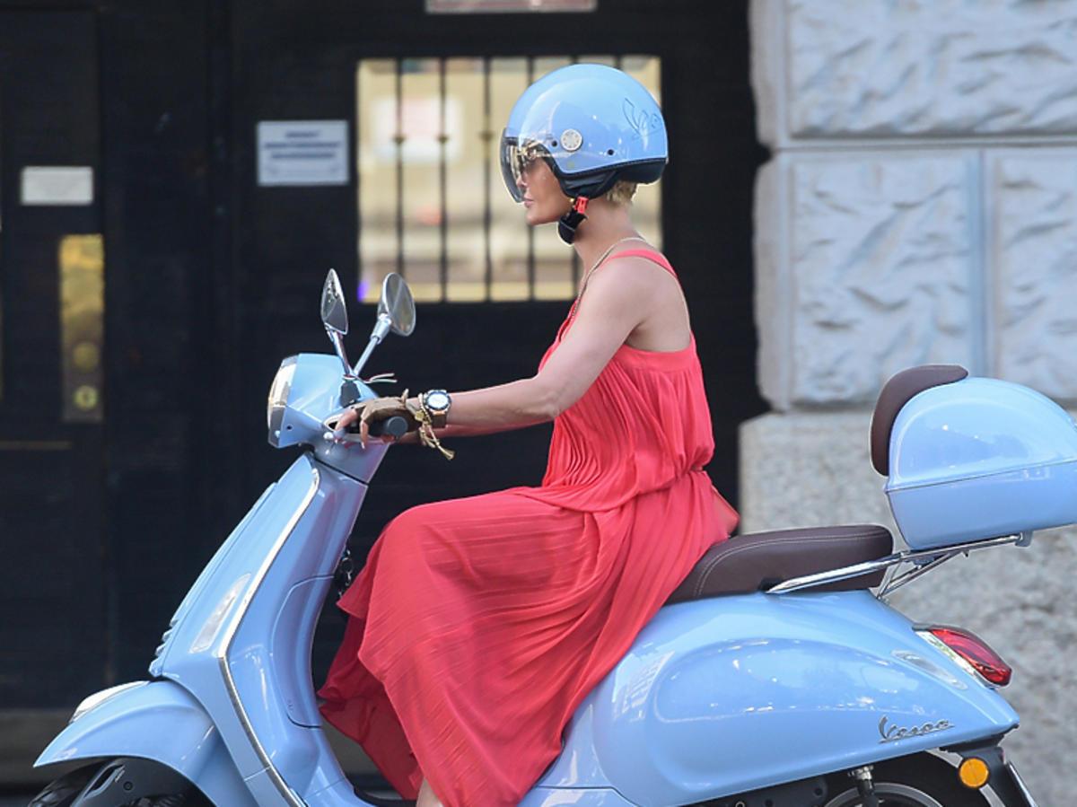 Joanna Racewicz w długiej sukni i szpilkach na skuterze