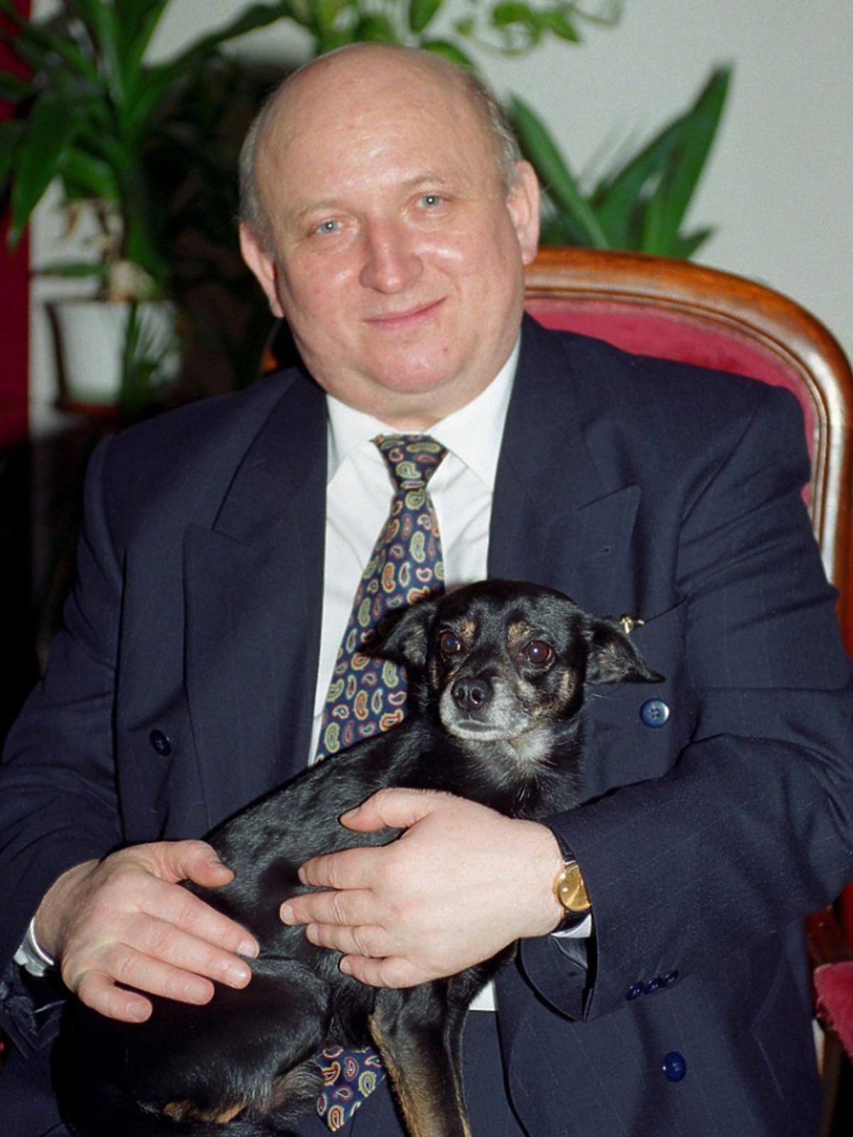 Józef Oleksy siedzi na fotelu z psem na kolanach, zdjęcie w domu