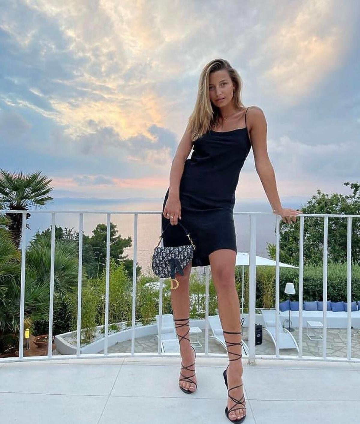 Julia Wieniawa w czarnej sukience i wiązanych sandałkach.