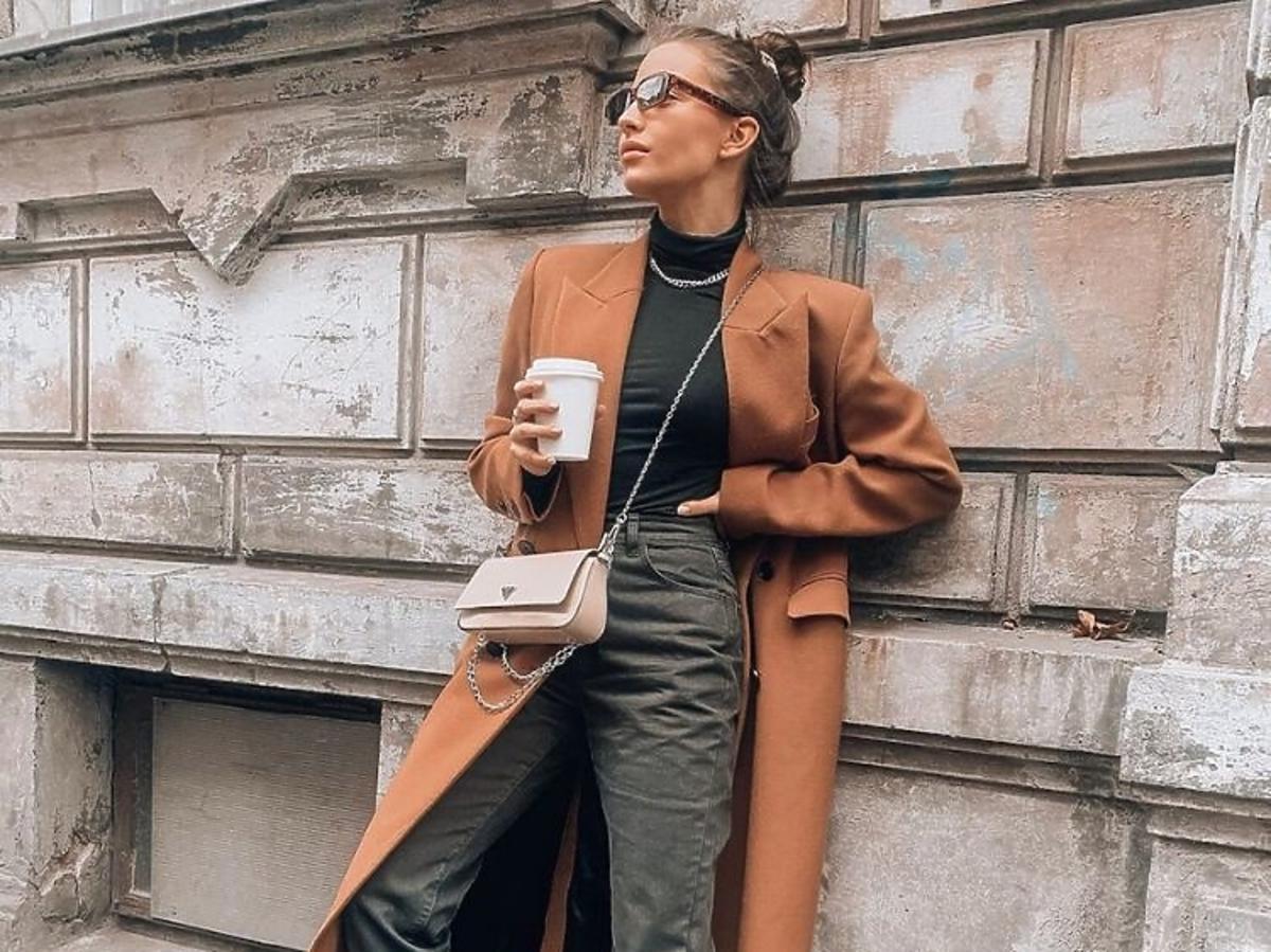 Julia Wieniawa w kaelowym płaszczu i wojskowych butach