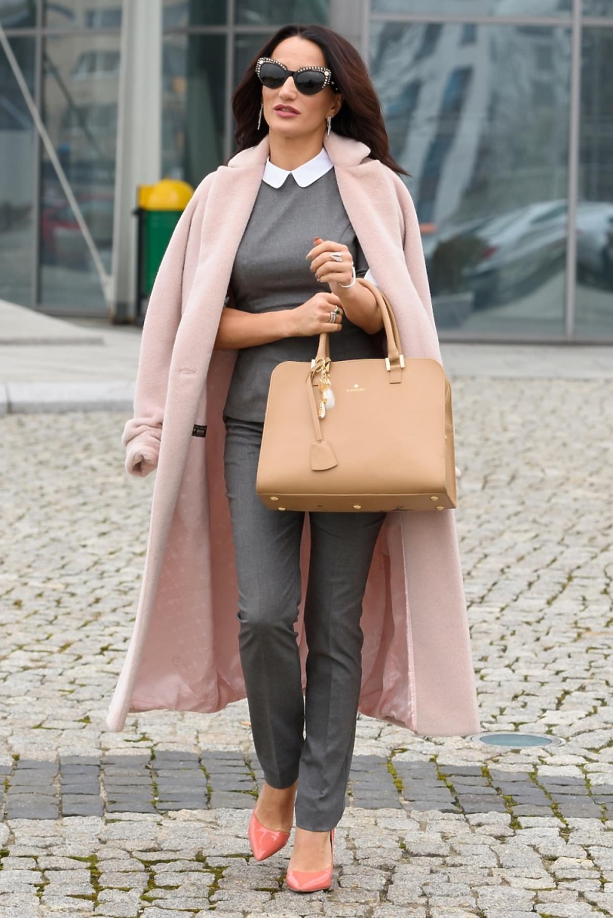 Justyna Steczkowska w ciemnych okularach i szarej bluzce z kołnierzykiem, różowym płaszczu i z beżową torbą