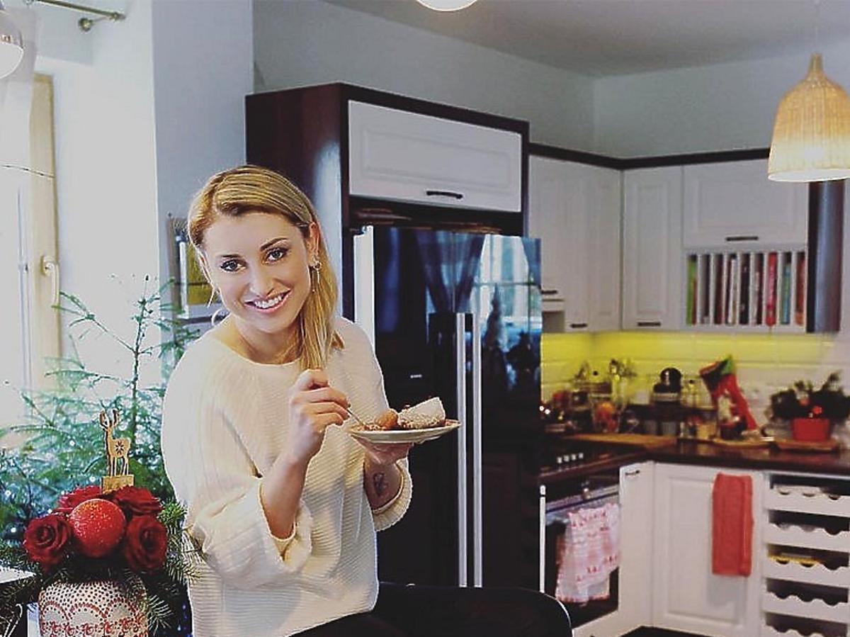 Justyna Żyła siedzi na stole w kuchni