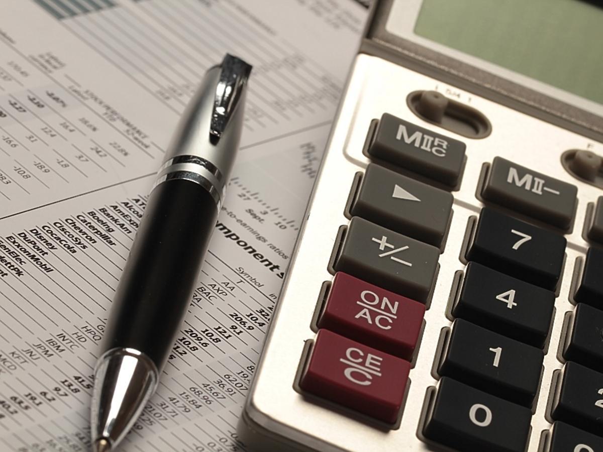 Kalkulator i długopis leżą na kartce papieru.