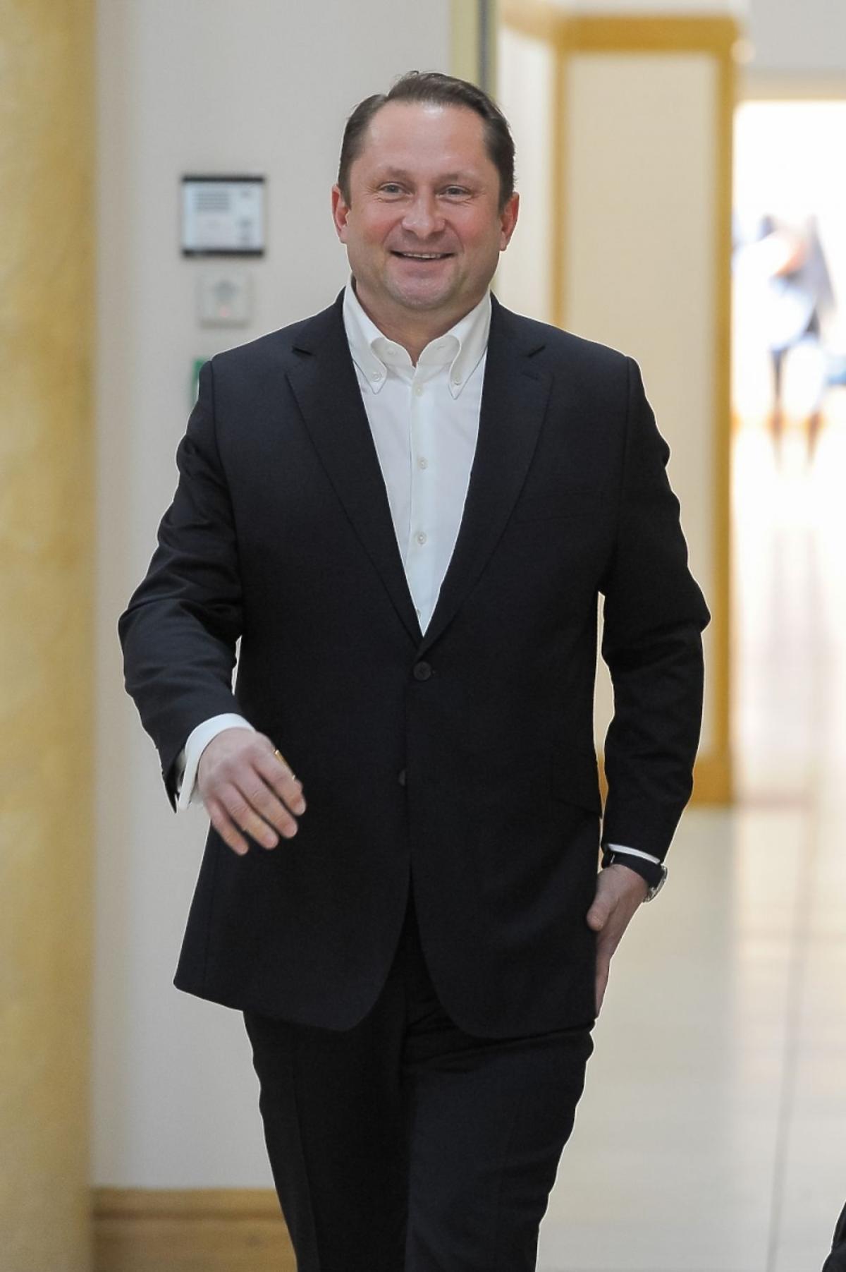 Kamil Durczok w czarnym garniturze i białej koszuli w sądzie