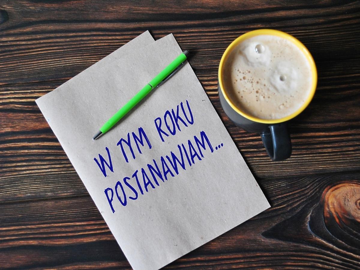 kartka z postanowieniami-noworocznymi i kubek z kawą