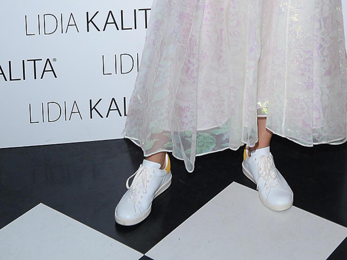 Kasia Sokołowska w długiej, metalicznej spódnicy i białych butach