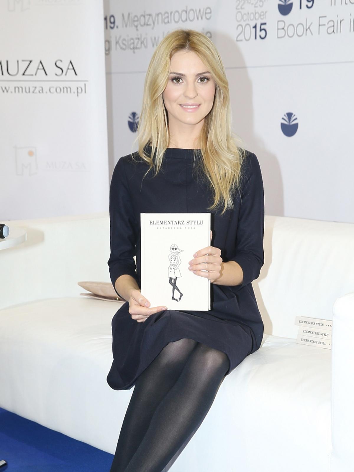 Kasia Tusk w czarnej sukience i czarnych butach siedzi ze swoją książką