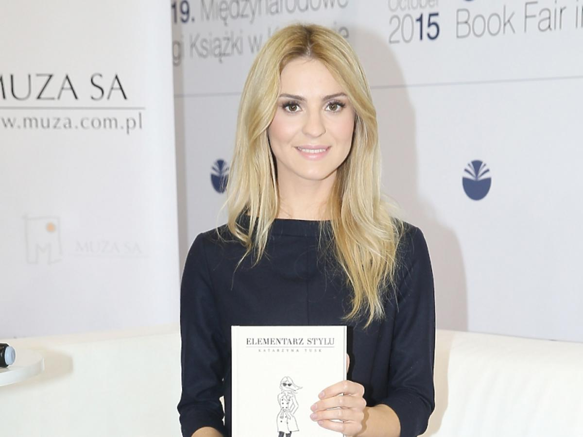 """Kasia Tusk w czarnej sukience i czarnych butach siedzi ze swoją książką """"Elementarz stylu"""" na Targach Książki"""