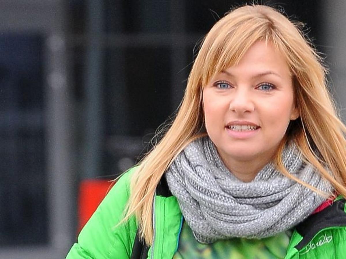 Katarzyna Bujakiewicz w zielonej kurtce i szaliku wychodzi ze studia TVP