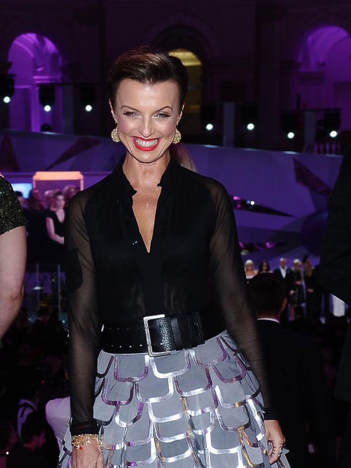 Katarzyna Sokołowska w czarnej bluzce, srebrnej spódnicy z małą torebką w kwiaty