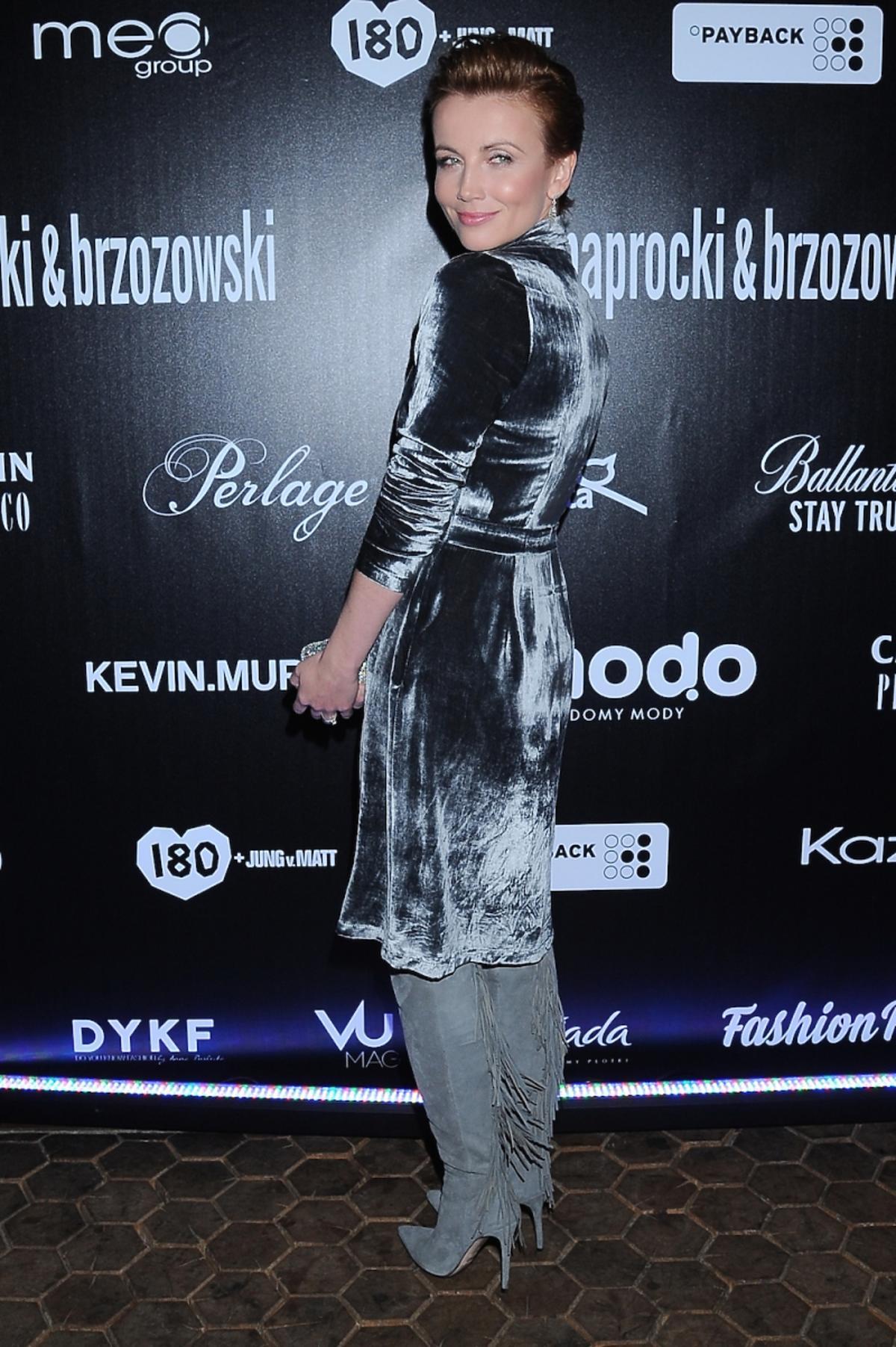 Katarzyna Zielińska w aksamitnej szarej sukience, kozakach z frędzlami z małą srebrną torebką