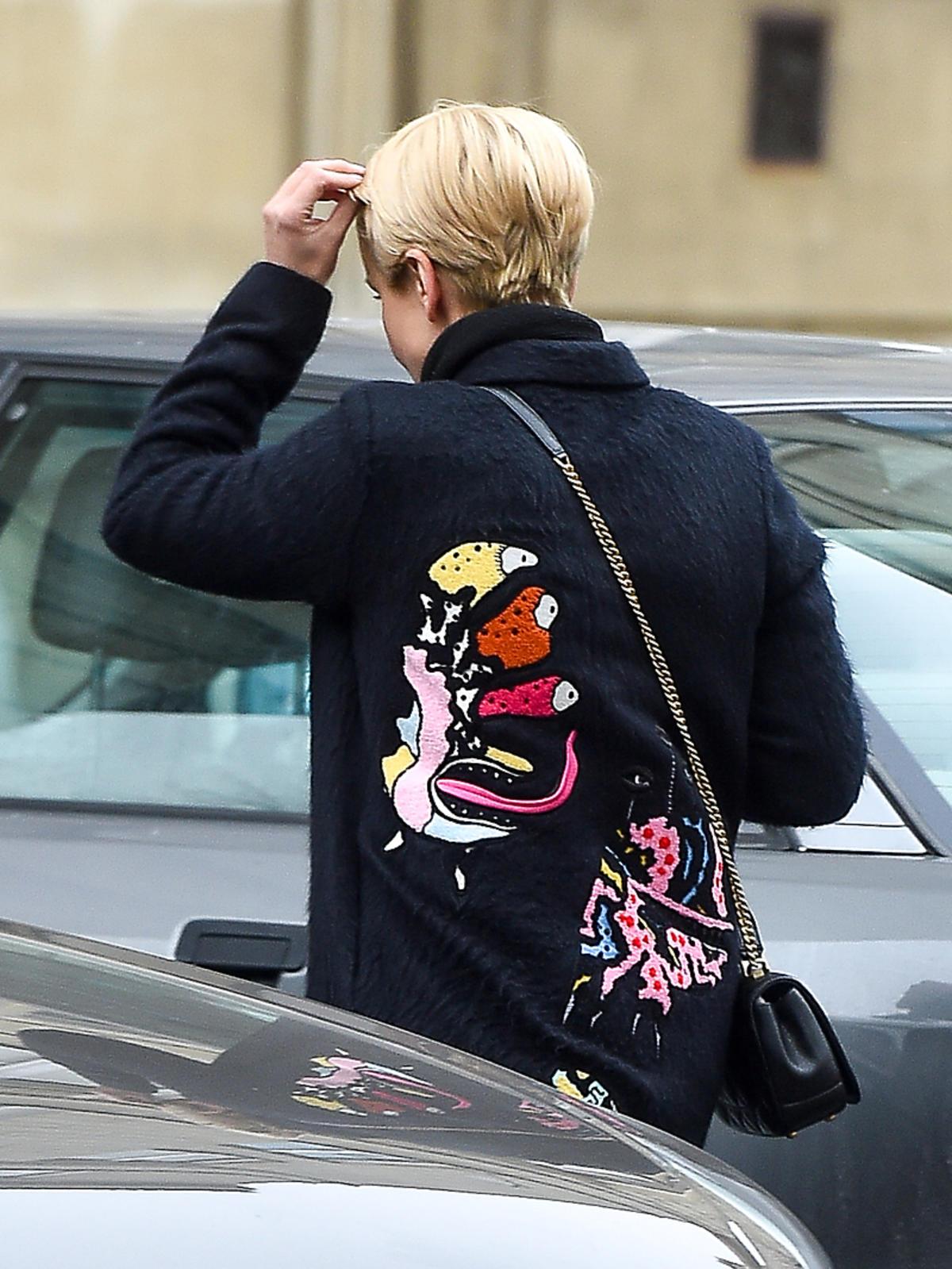 Katarzyna Zielińska w czarnym płaszczu z potworkami na plecach