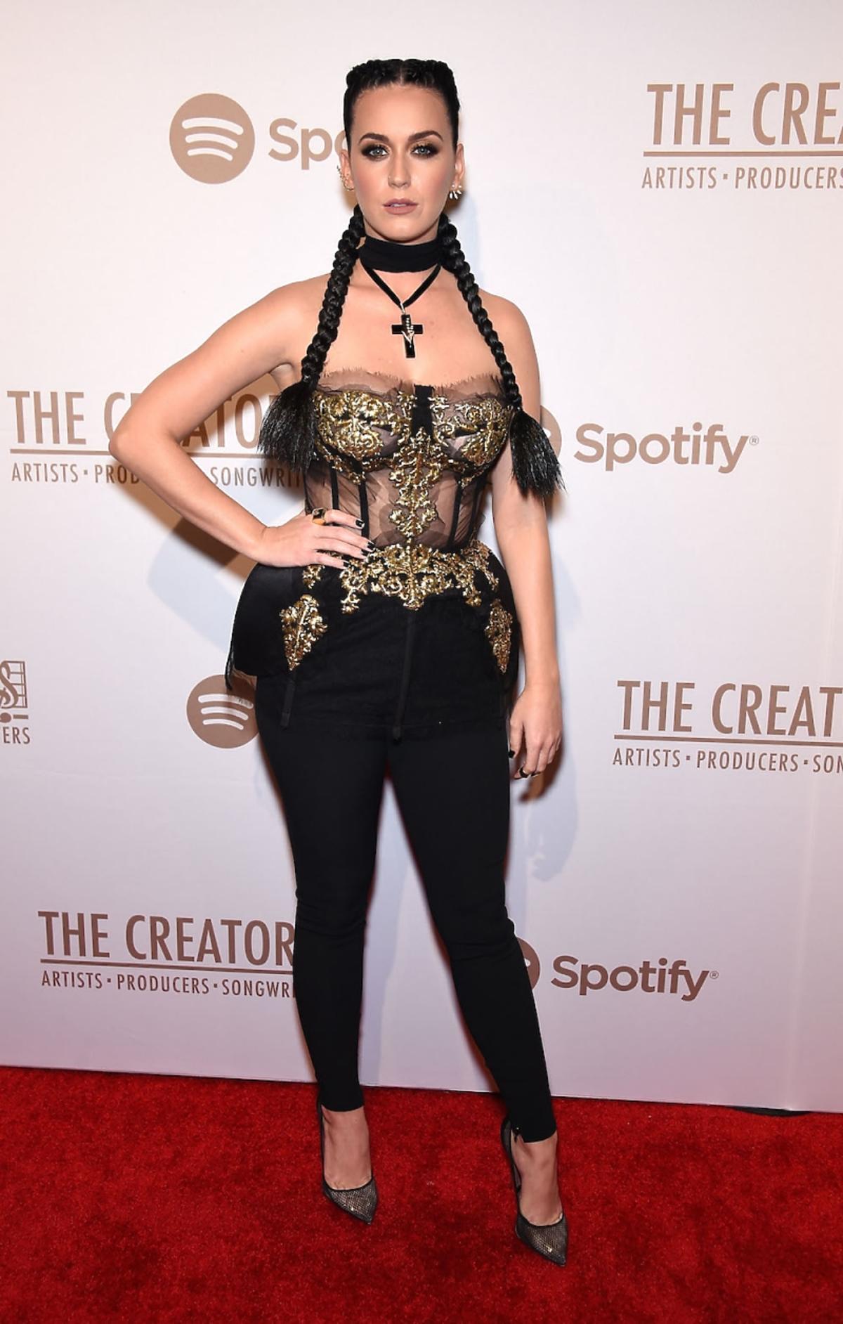 Katy Perry w czarno-złotym gorsecie i czarnych spodniach, z czarnymi długimi warkoczami