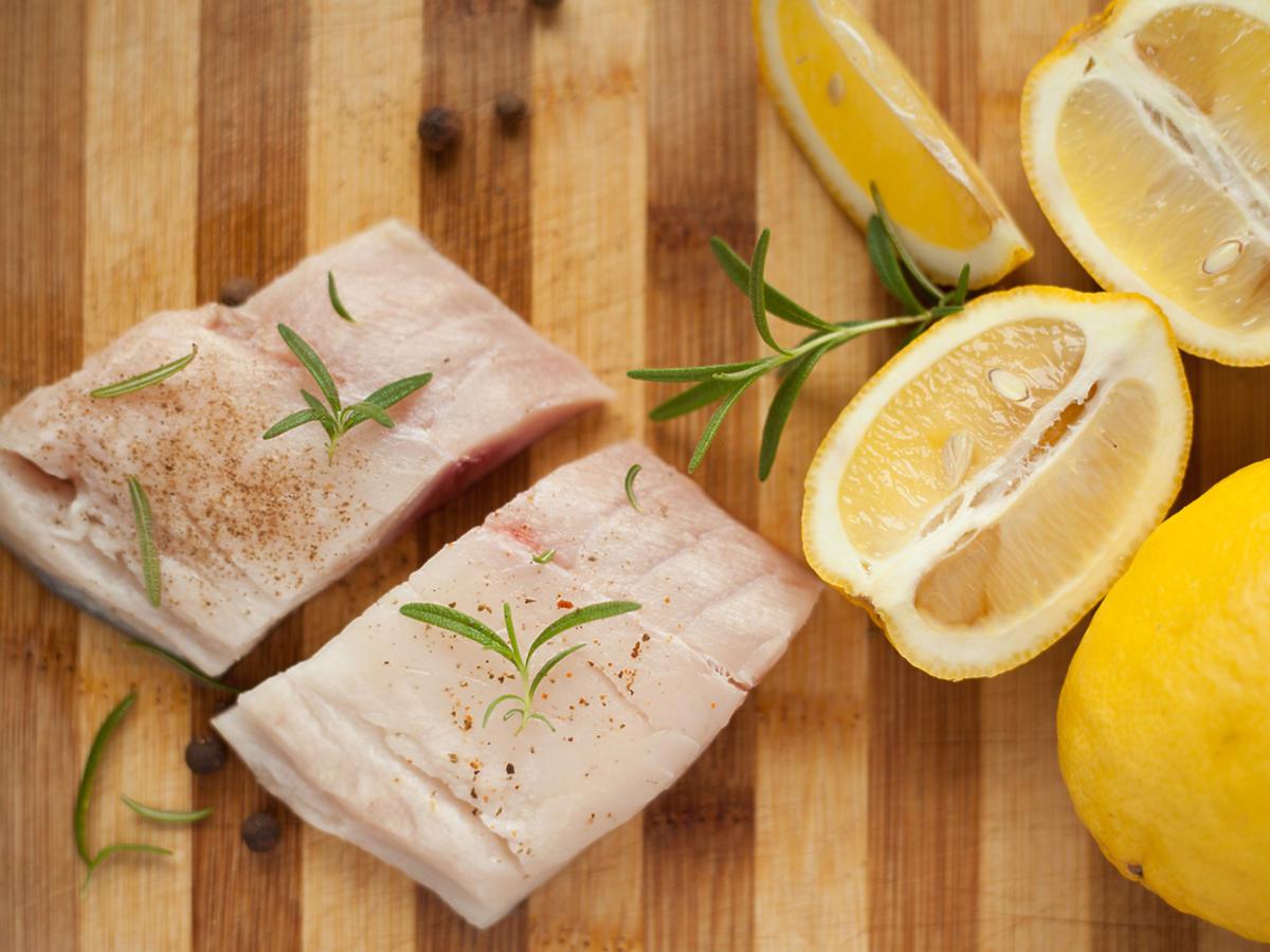 Kawałki dorsza położone na blacie i pokropione sokiem z cytryny.