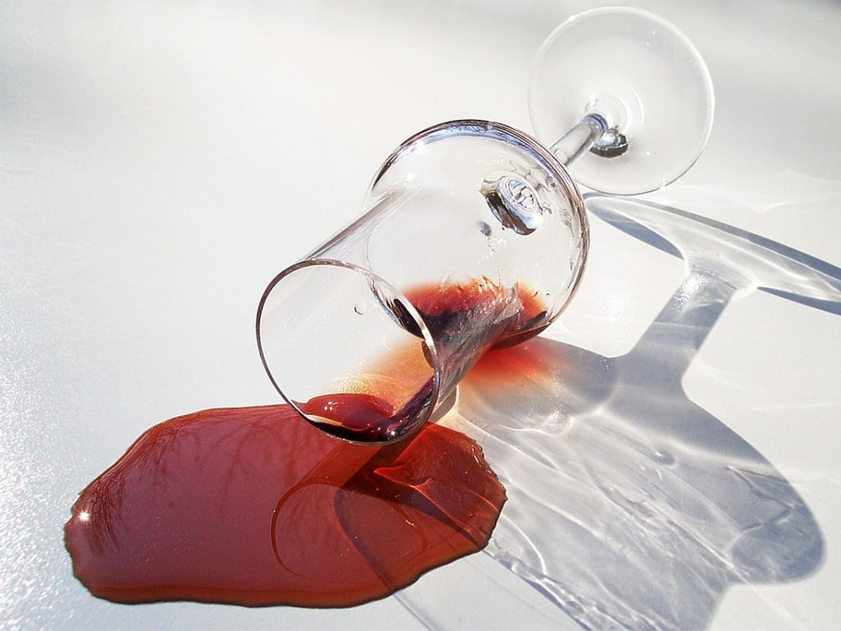 kieliszek wylanego czerwonego wina