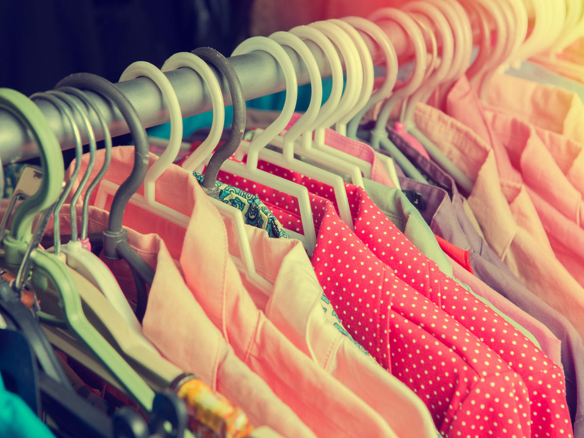Kilka kolorowych koszul wisi na wieszaku.