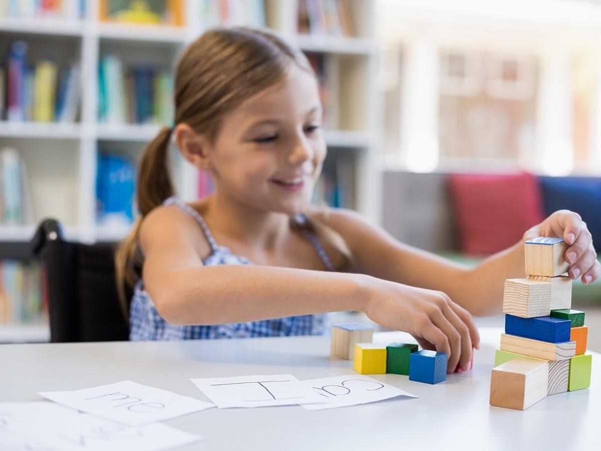 Kilkuletnia dziewczyna bawi się klockami na stole.