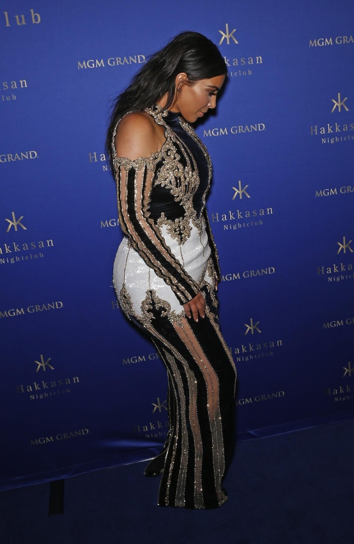 Kim Kardashian w długiej sukni w czarno-złote pasy z odkrytymi ramionami i białym materiałem na biodrach