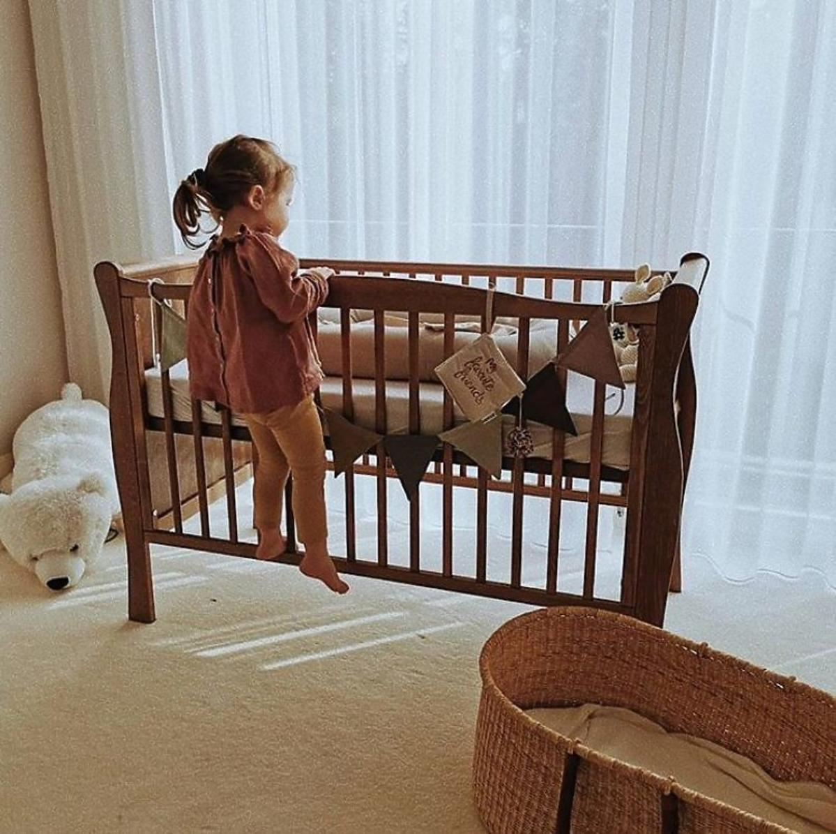 Klara Lewandowska wchodzi do łóżeczka dziecięcego