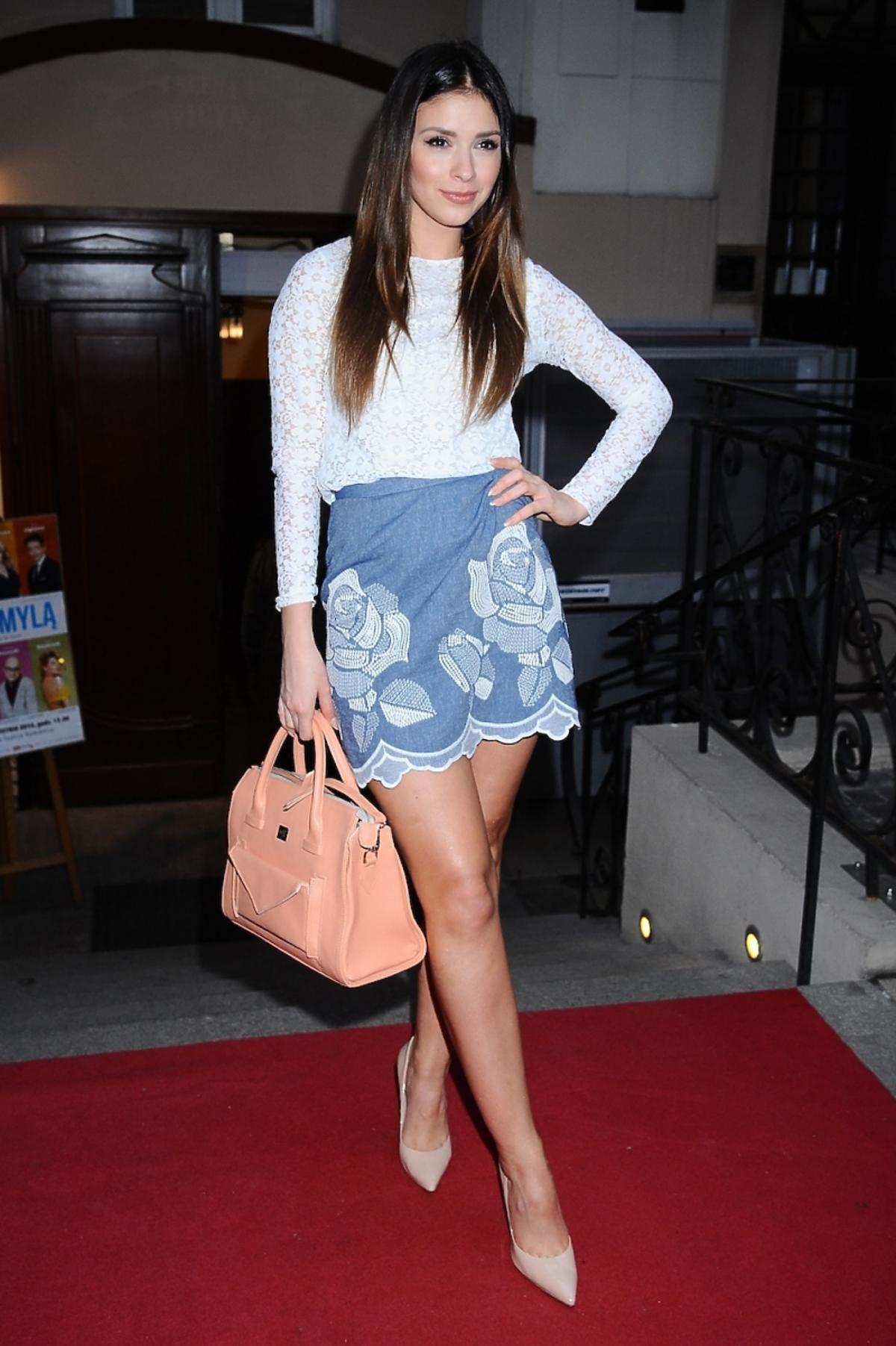 Klaudia Halejcio w dżinsowej minispódnicy i białej bluzce z morelową torbą