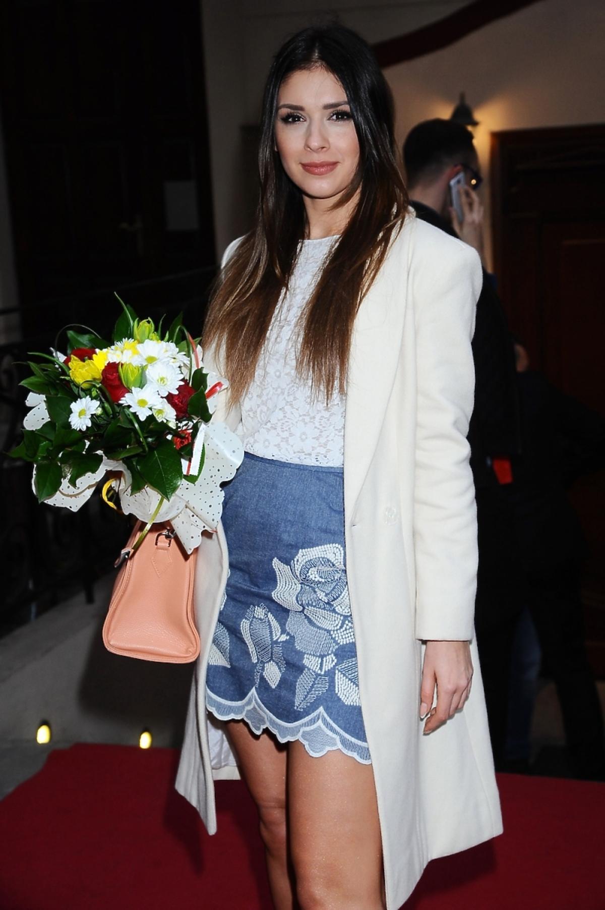 Klaudia Halejcio w dżinsowej minispódnicy i białej marynarce z bukietem kwiatów