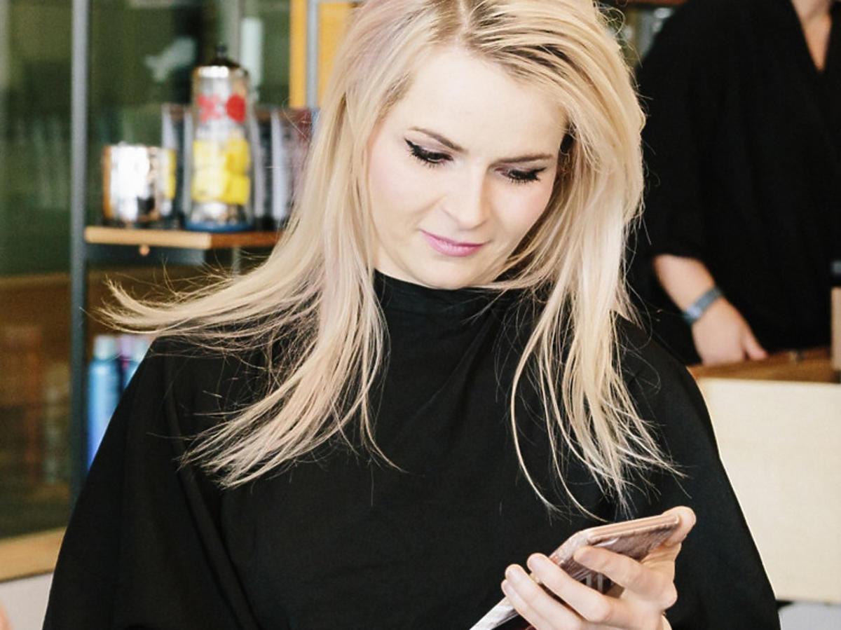 Klientka z blond włosami w salonie fryzjerskim