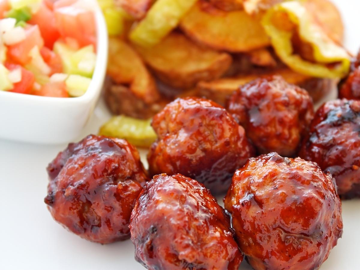 Klopsiki z mięsa mielonego na tle ziemniaków i sałatki.