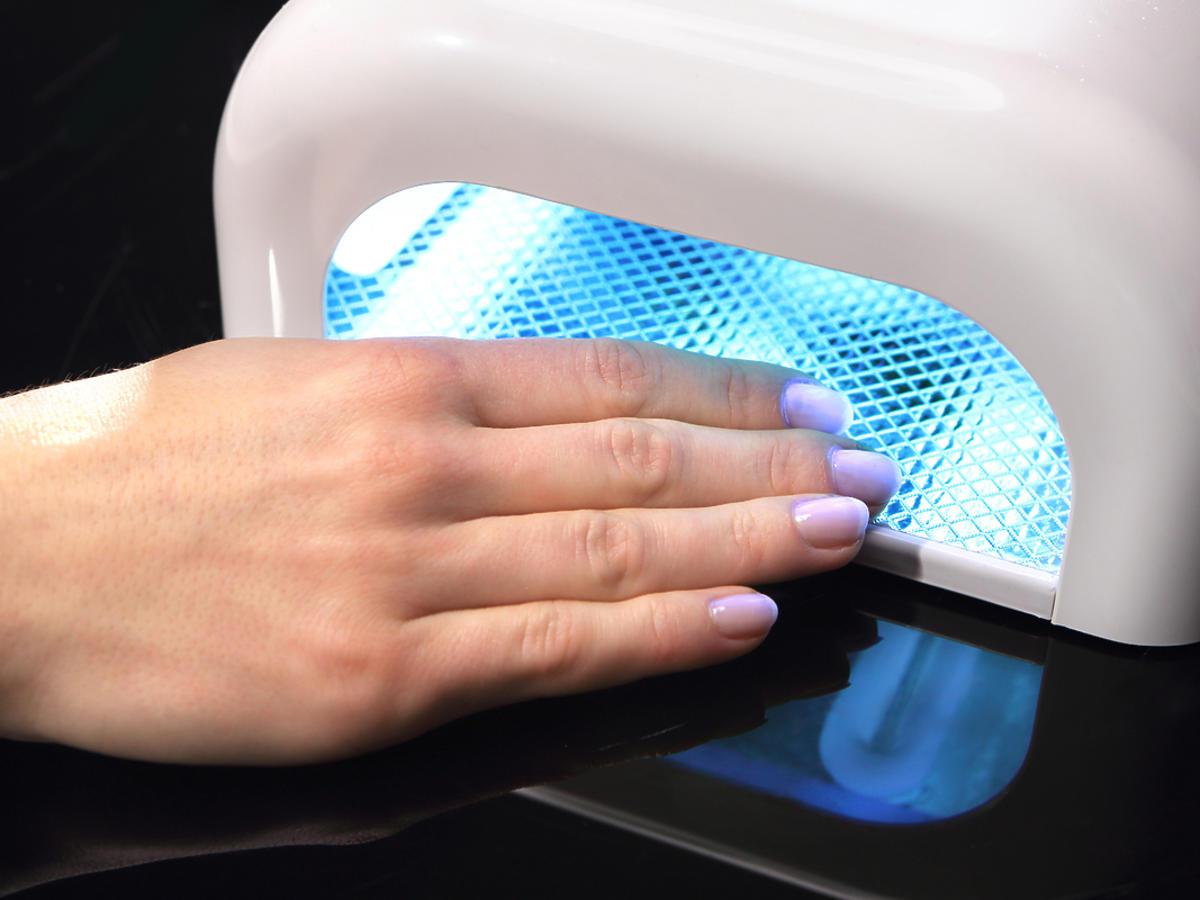 kobieca dłoń pod lampą do manicure hybrydowego