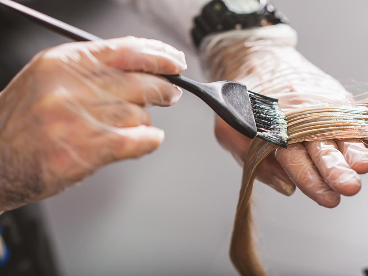 kobieca dłoń z pędzelkiem do malowania włosów