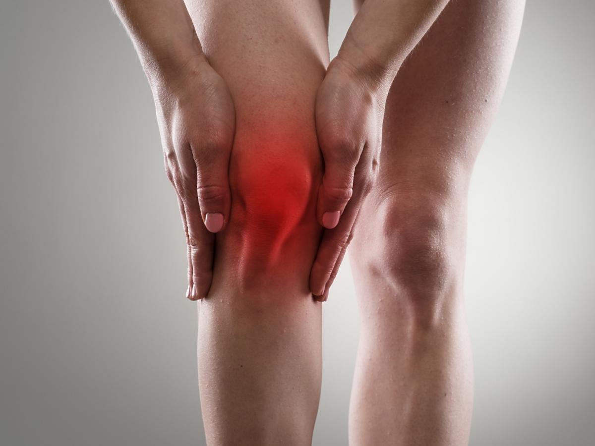 kobiece dłonie wokół czerwonego, bolącego kolana