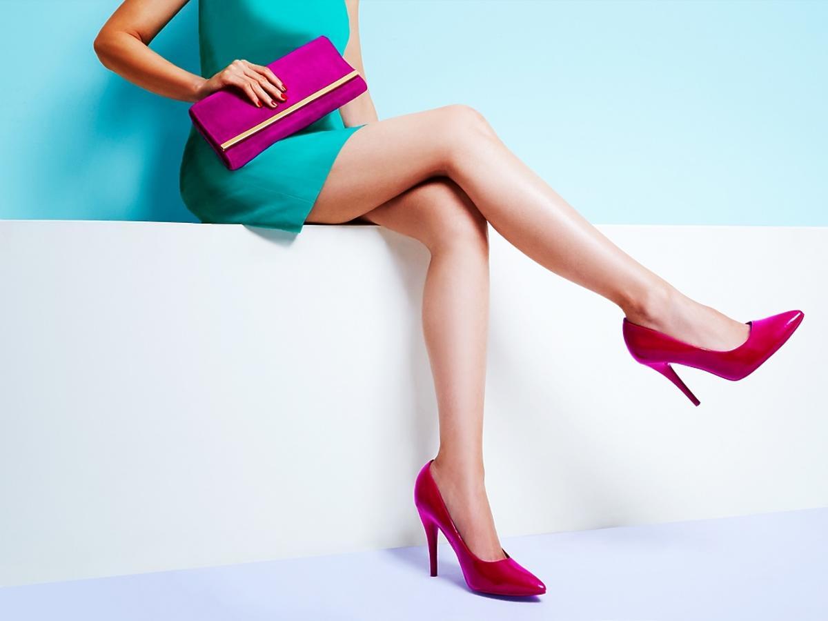 Kobiece nogi w różowych szpilkach na jasnym tle.