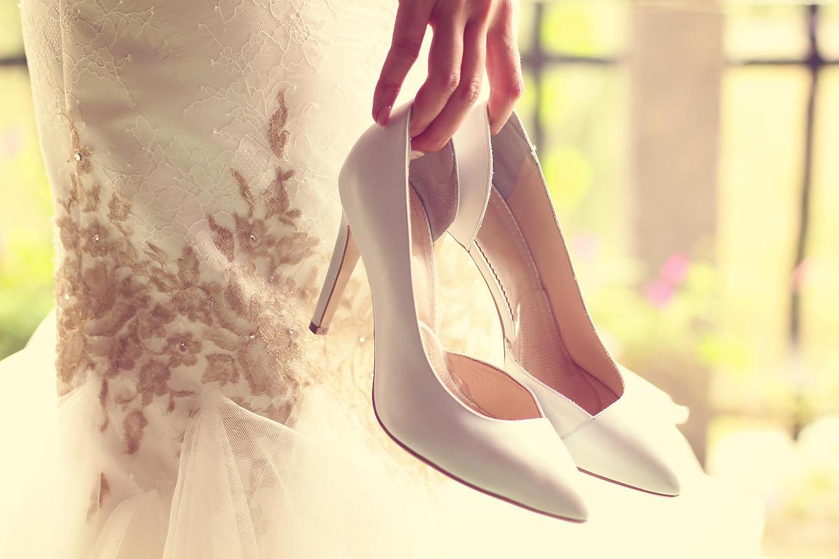 panna młoda trzymająca w ręce buty na wysokiej szpilce