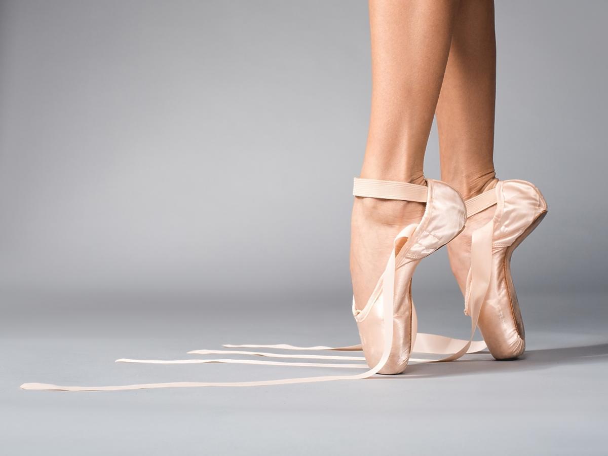 Kobiece stopy w różowych baletkach