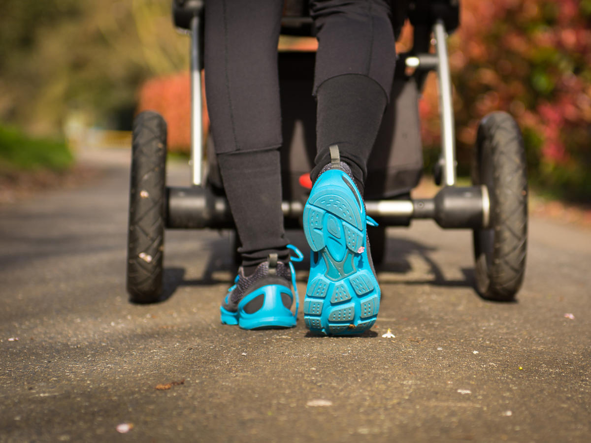 Kobieta biega pchając wózek dziecięcy.