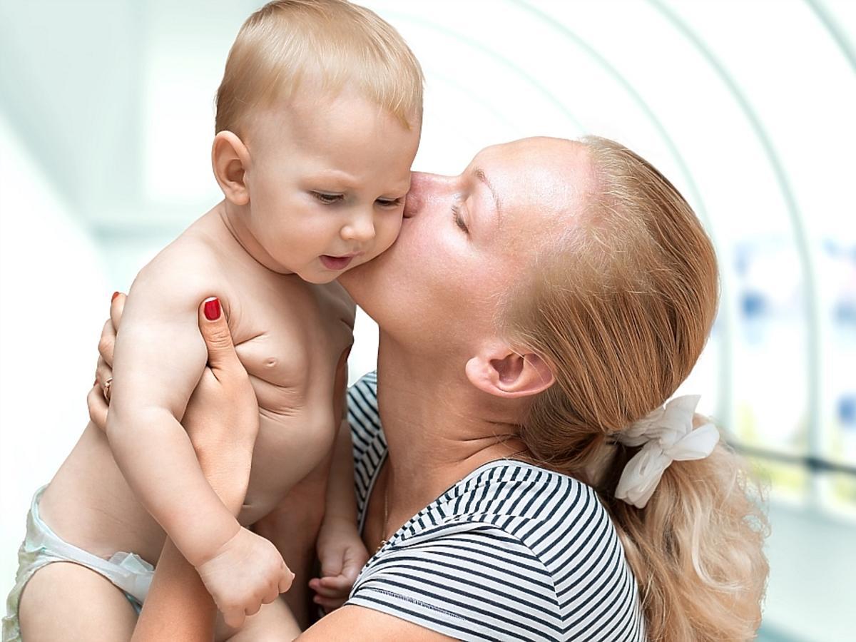 kobieta całuje niemowlę