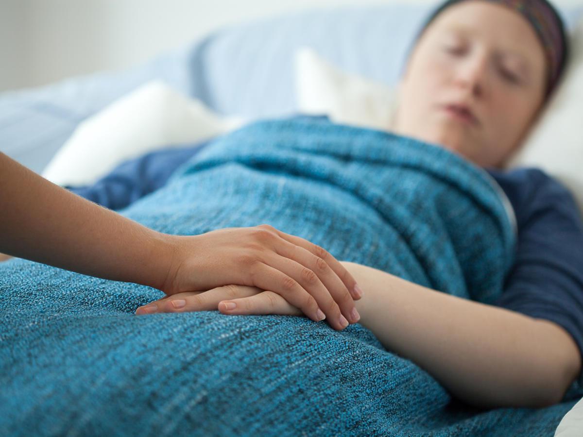 Kobieta chora na białaczkę leży na łóżku