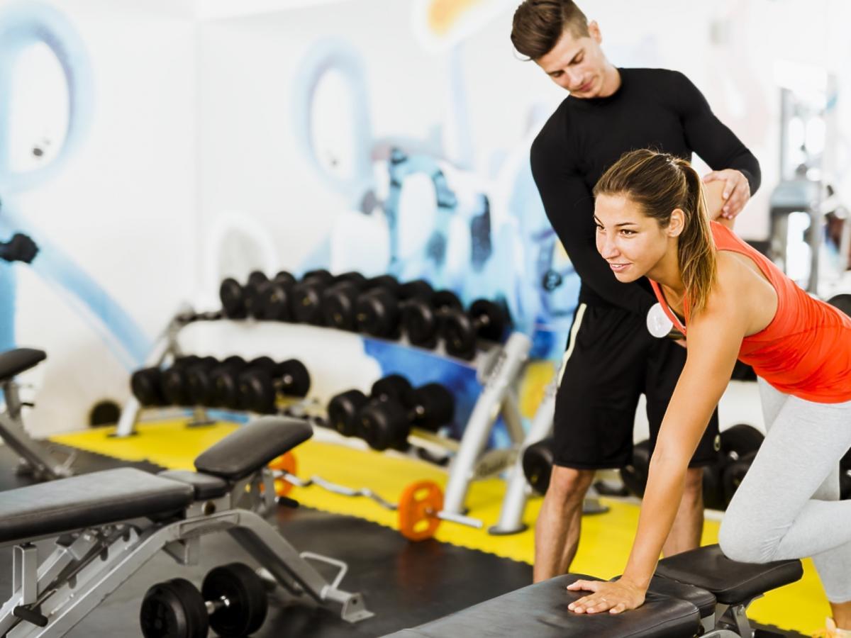 kobieta ćwiczy na ławeczce na siłowni pod okiem instruktora