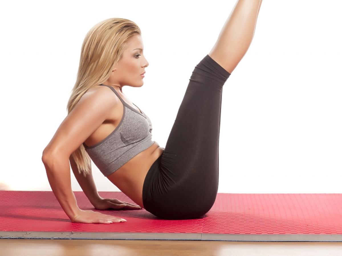 Kobieta ćwiczy unosząc obie nogi.